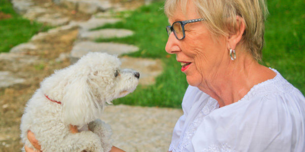 older woman holding her fluffy white poodle and talking happily