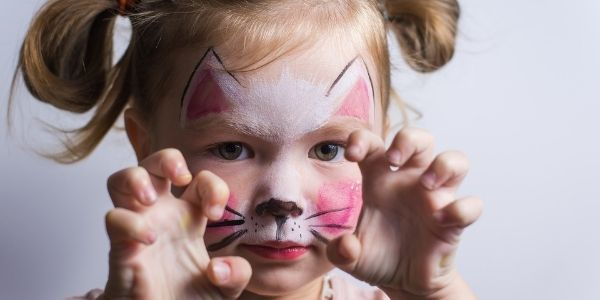 young child face painted like a cat